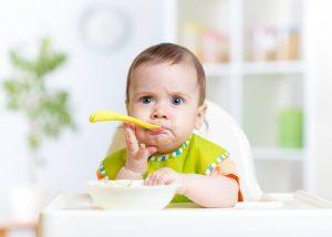 Baby girl eating food on kitchen