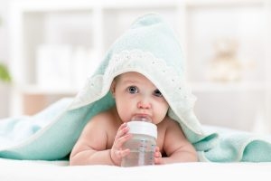 baby drinking from bottle, wrapped in a towel